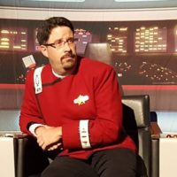 Tony Hunter in a Starfleet Monster Maroon Uniform sitting on a Captain's chair